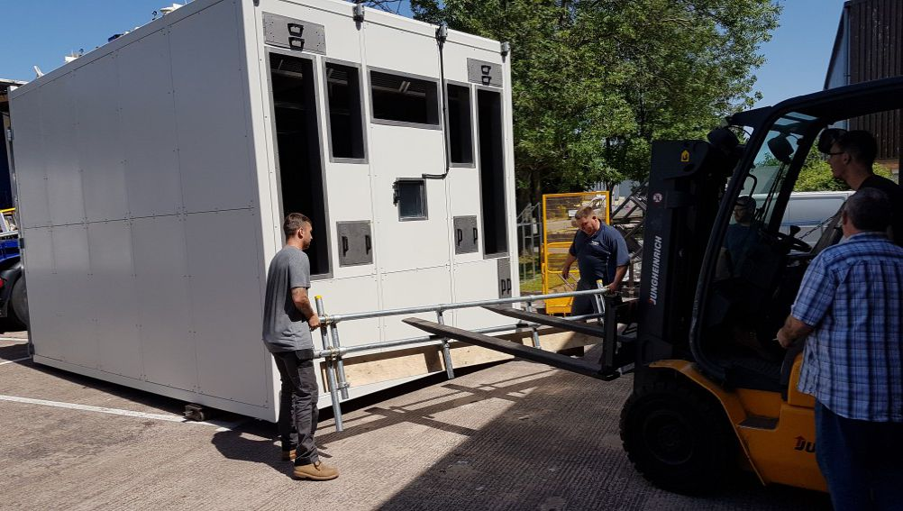 four men and a forklift moving a very large test chamber outside in sunshine