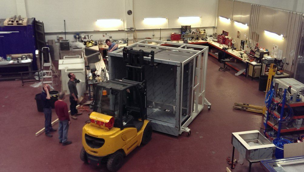 tyhe frame of a test chamber being moved with a fork lift truck