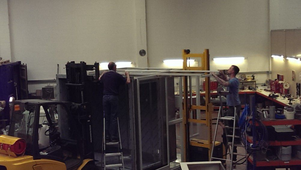 two men constructing the frame of a test chamber
