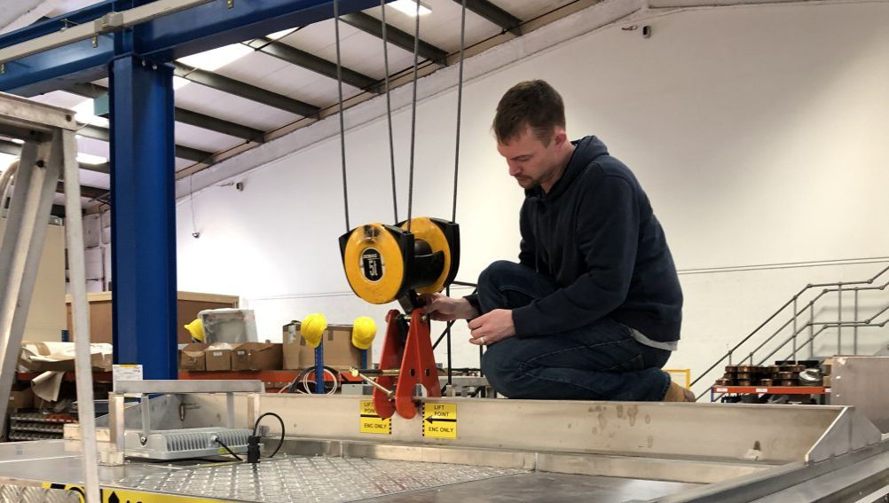 man attaching large test chamber to a hoist